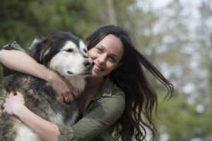 A woman hugging her dog.